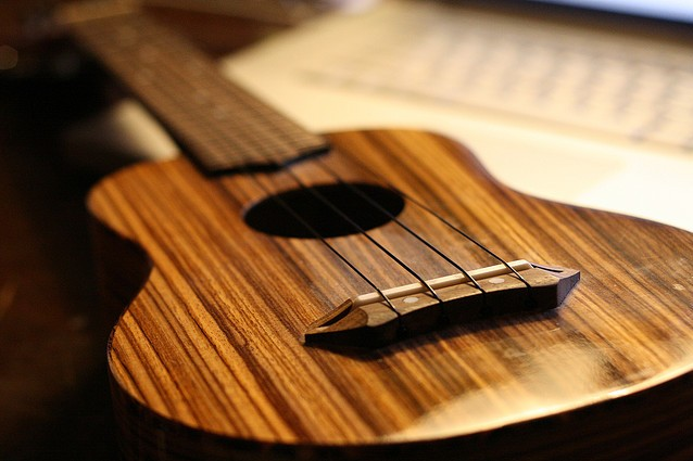 a close up photo of a ukulele with a sheet of music in the background.