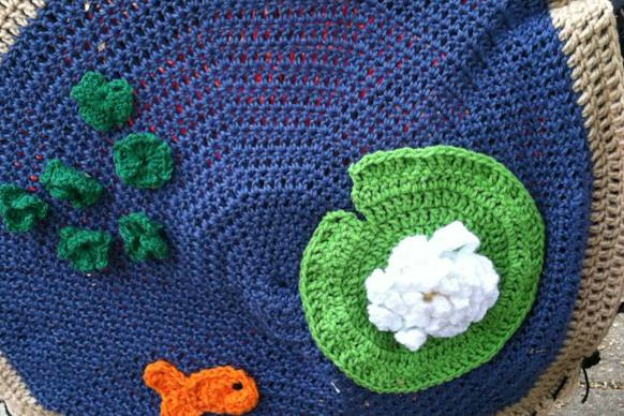 a circle of detail knitting in the style of a fish pond with lilypad and gold fish