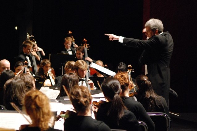 a conductor points over the heads of the orchestra on stage