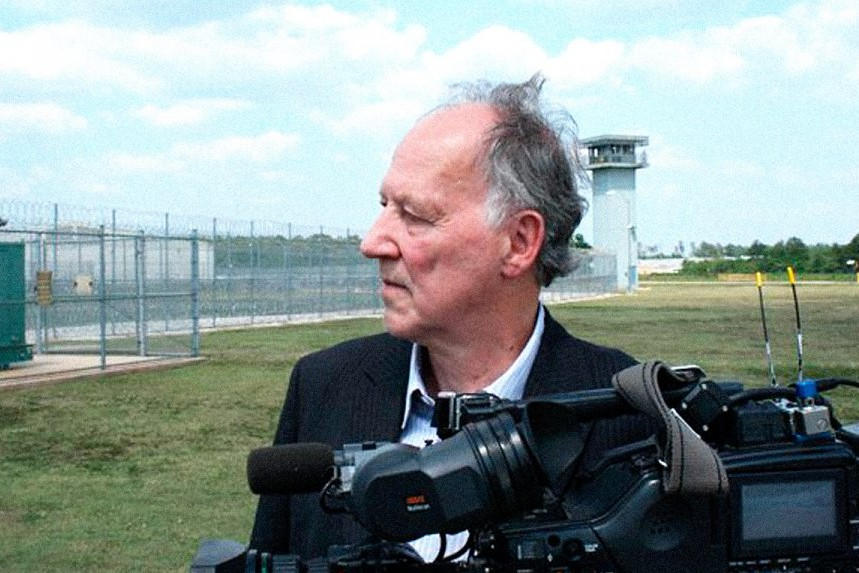 a man outside a prison with a video camera