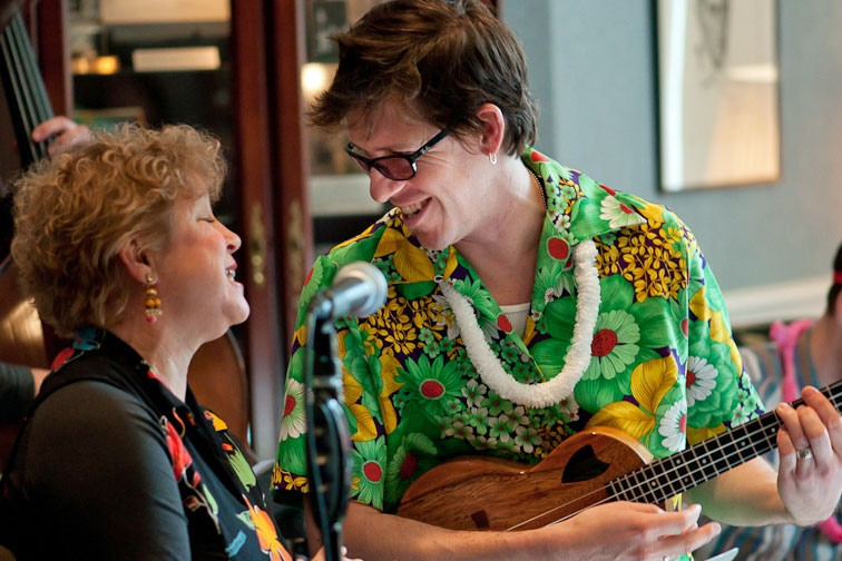 a woman sings and a man plays ukulele in a hawaiian shirt