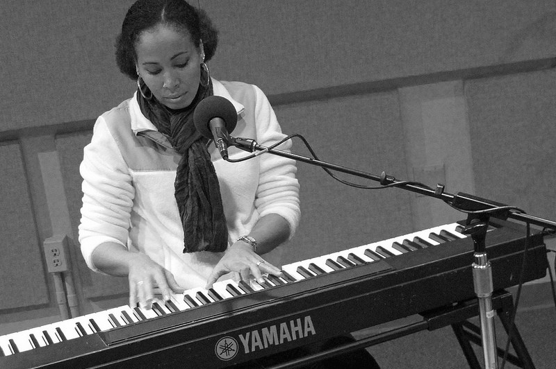 a woman sits at a piano with a microphone.