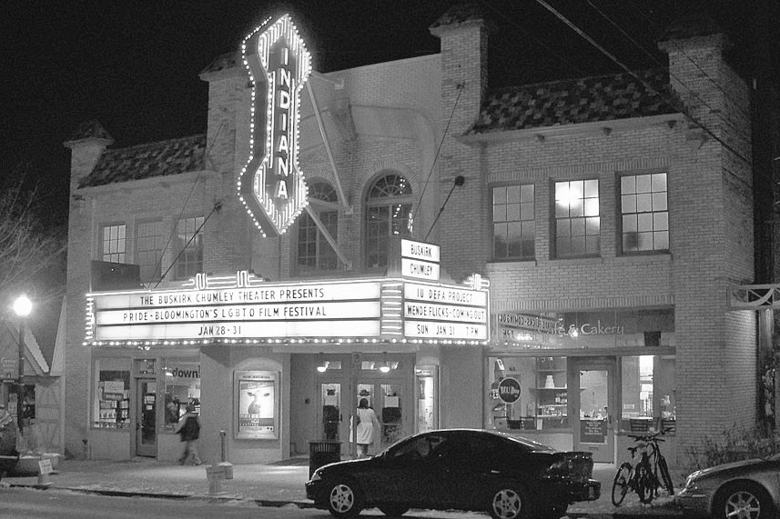 a black and white photo of a theater marquee from the street
