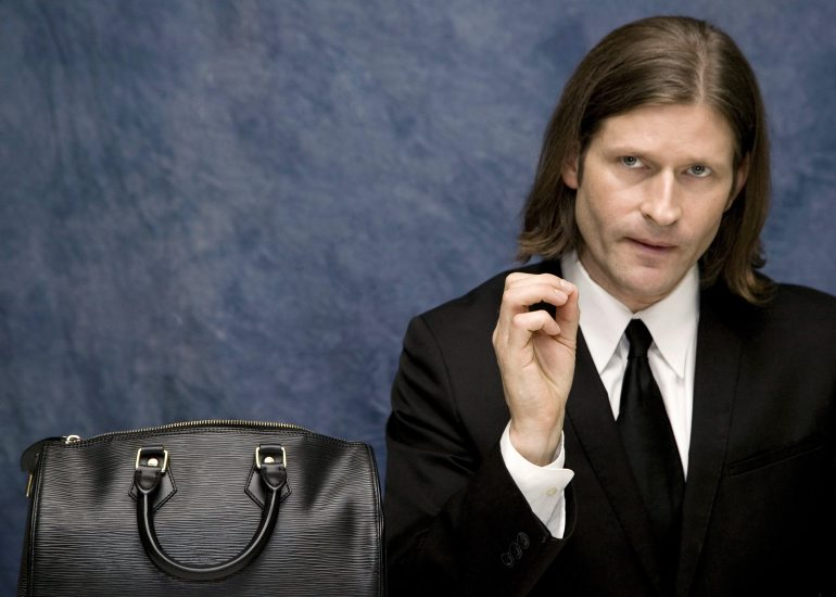 a man in a suit sits in front of a blue wall with a black handbag beside him