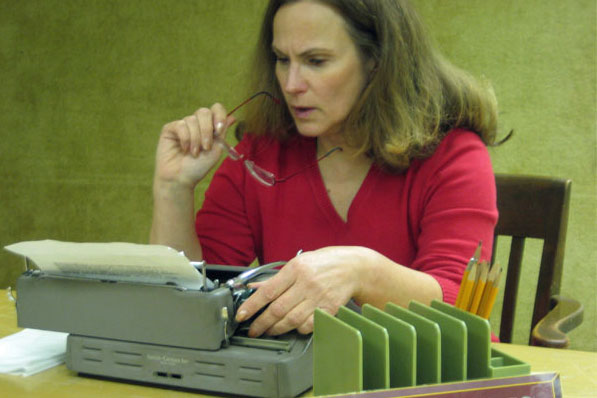a woman sits at a typewriter