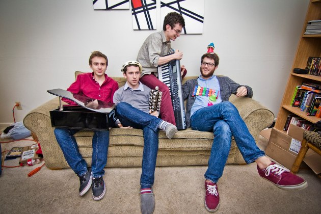 a group of men sit on a couch with instruments