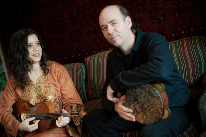 a women sits holding a viola and a man sits holding a hand drum.