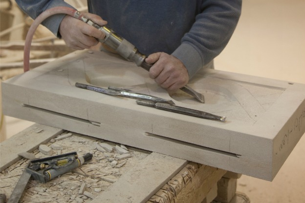 hands of limestone cutter at work on an ornamental relief panel