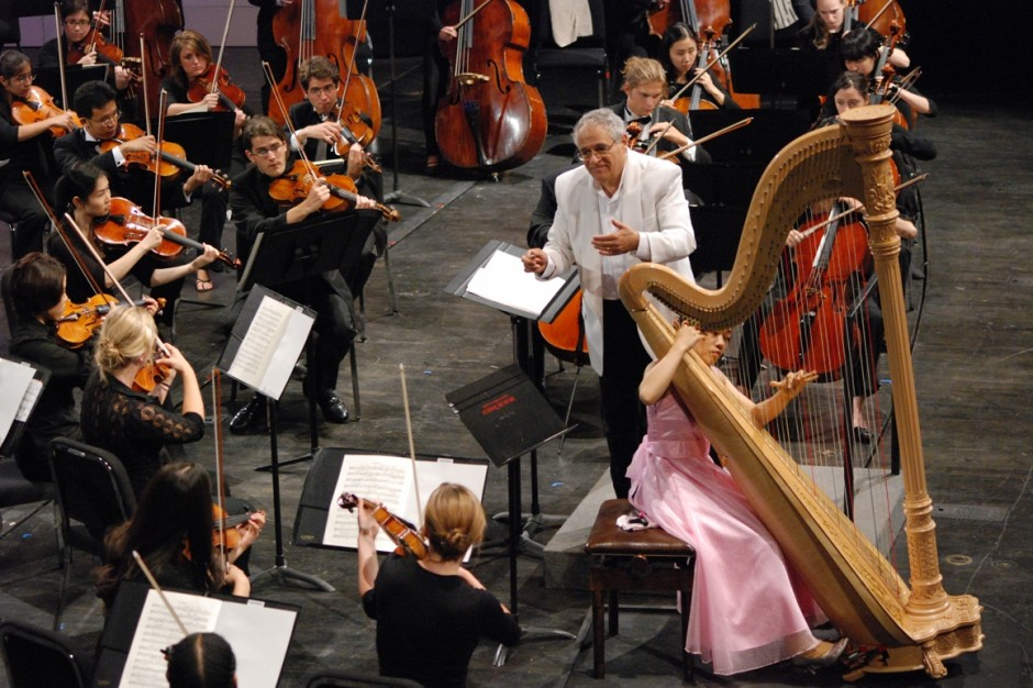 a woman in a pink dress plays a harp on stage with a full orchestra