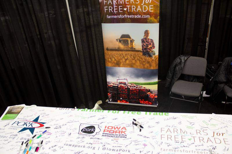 A display at a table at a farm trade show. Many signatures and a sharpie on a banner on the table, with logos of companies.