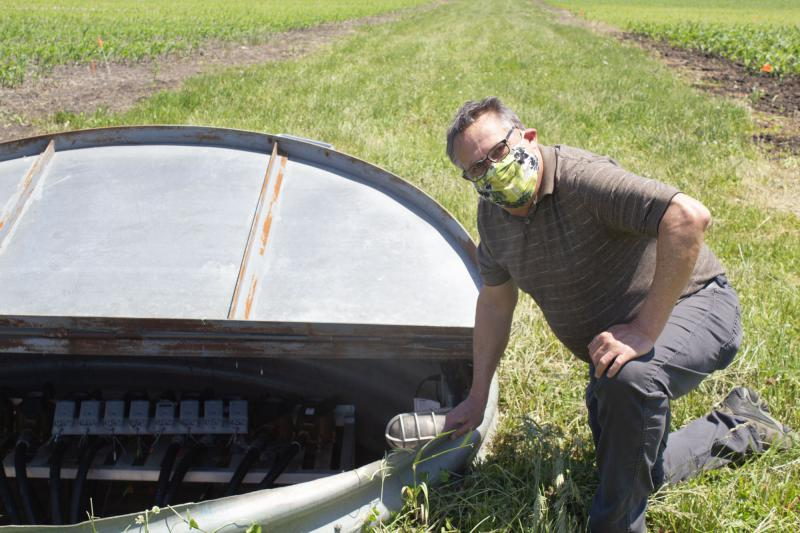 Tom Moorman, wearing a face mask, kneels beside a metal lined pit in a green field.