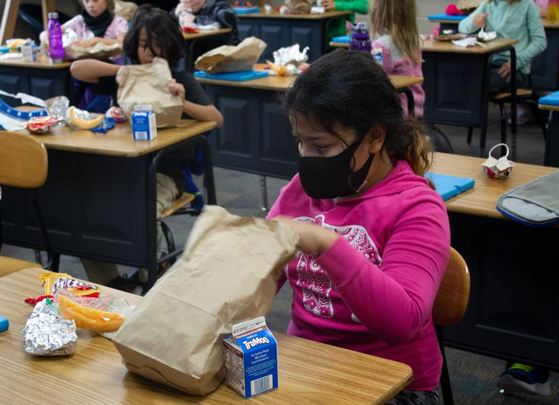 A girl in a bright pink shirt with a black face mask unpacks a sack lunch at a desk in a classroom. Other students are in the background