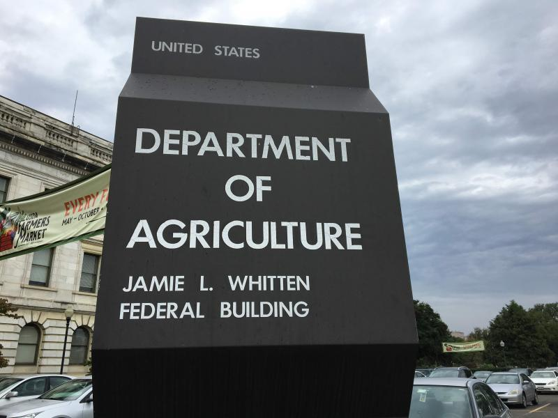 US Department of Agriculture Sign, in from of an historic building with cloudy skies in the background.