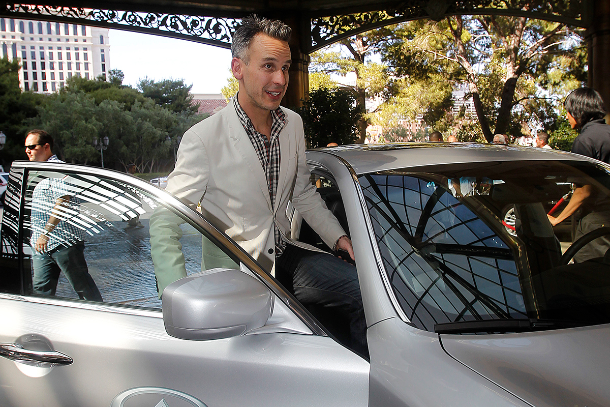 Adam Rappaport in a white blazer getting into a white car under an ornate carport.