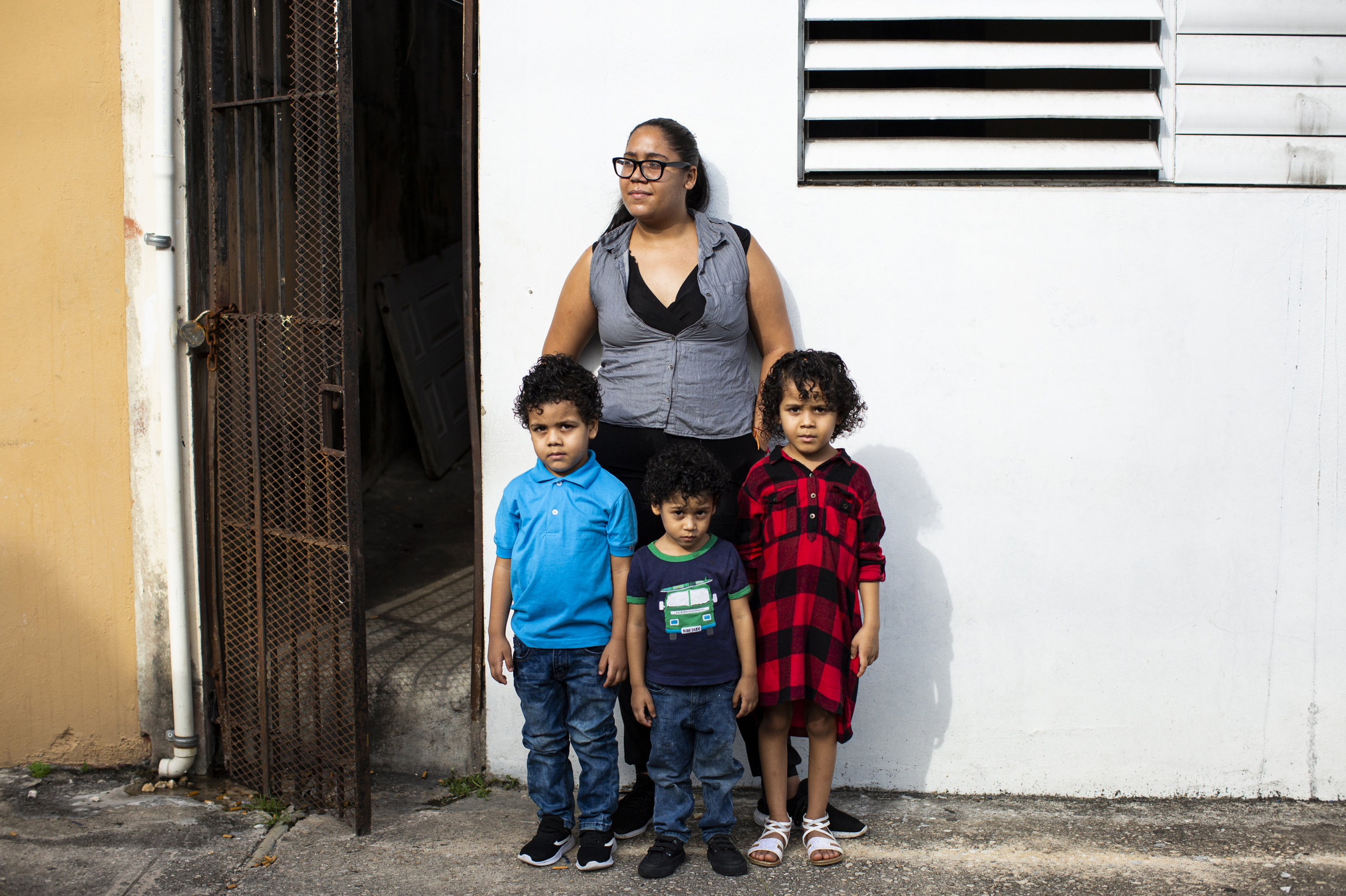 Elia Gonzalez stands with her children, Jesiel, Ansiel and Angellia, in front of a white wall with a vent, next to a metal-grated door.