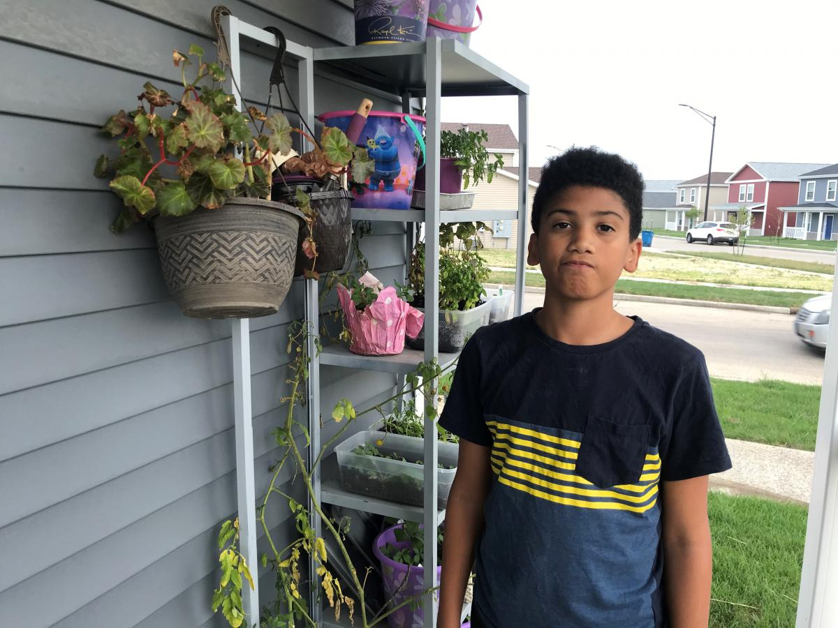 Joshua Pleasure stands on a porch in front of a shelf of plants.