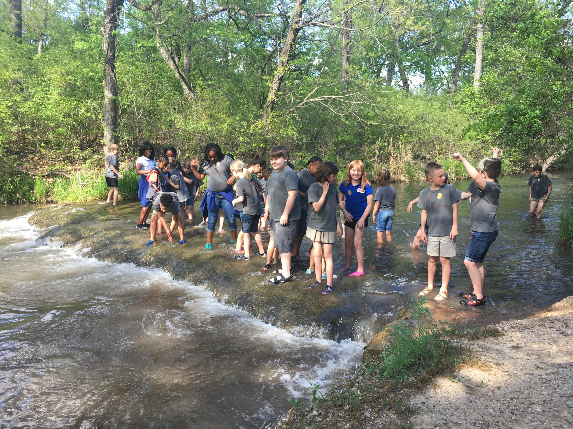 A large group of school-aged kids in gray t-shirts and shortsstanding in a wide shallow creek, smiling and laughing.