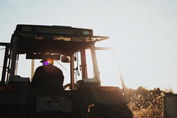 A backlit view of a person in the cab of a tractor.