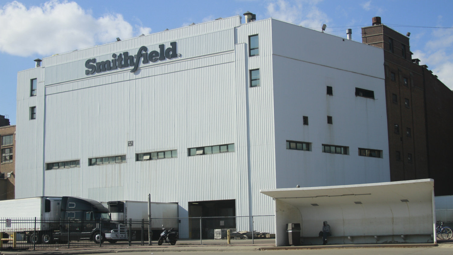 The front of a large, pale gray warehouse with the word 'Smithfield' across the top in dark gray
