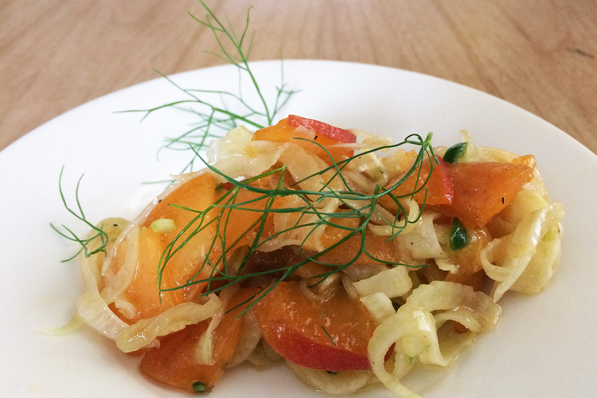 apricot and fennel salad on a white plate with fennel frond garnish
