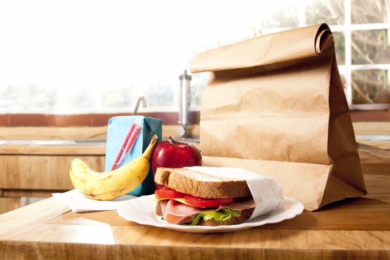 Staged photo of a ham and cheese sandwich, banana, apple, juicebox and a small paper sack, all on a well-lit kitchen counter.