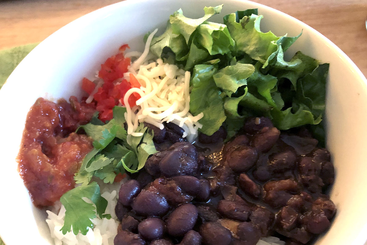 A white bowl with cooked black beans topped with cheese, lettuce, salsa, cilantro.
