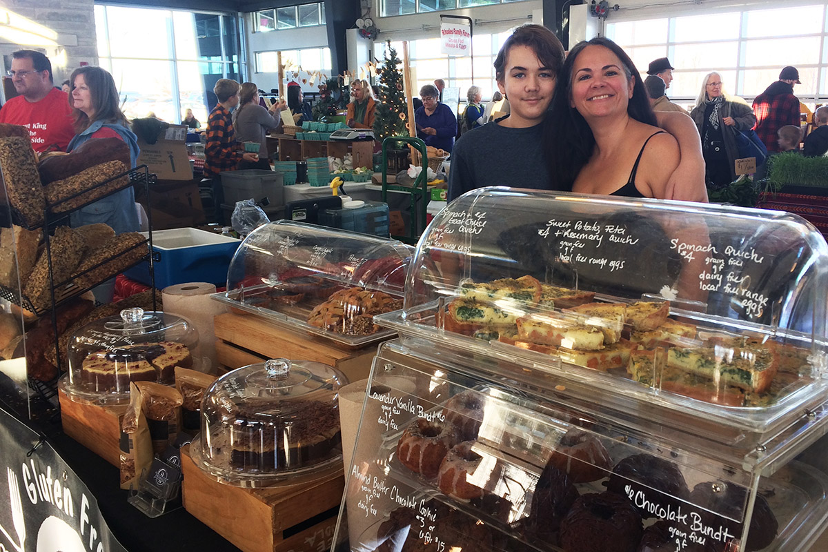 A woman and her teenage son at a booth of baked goods at an indoor market