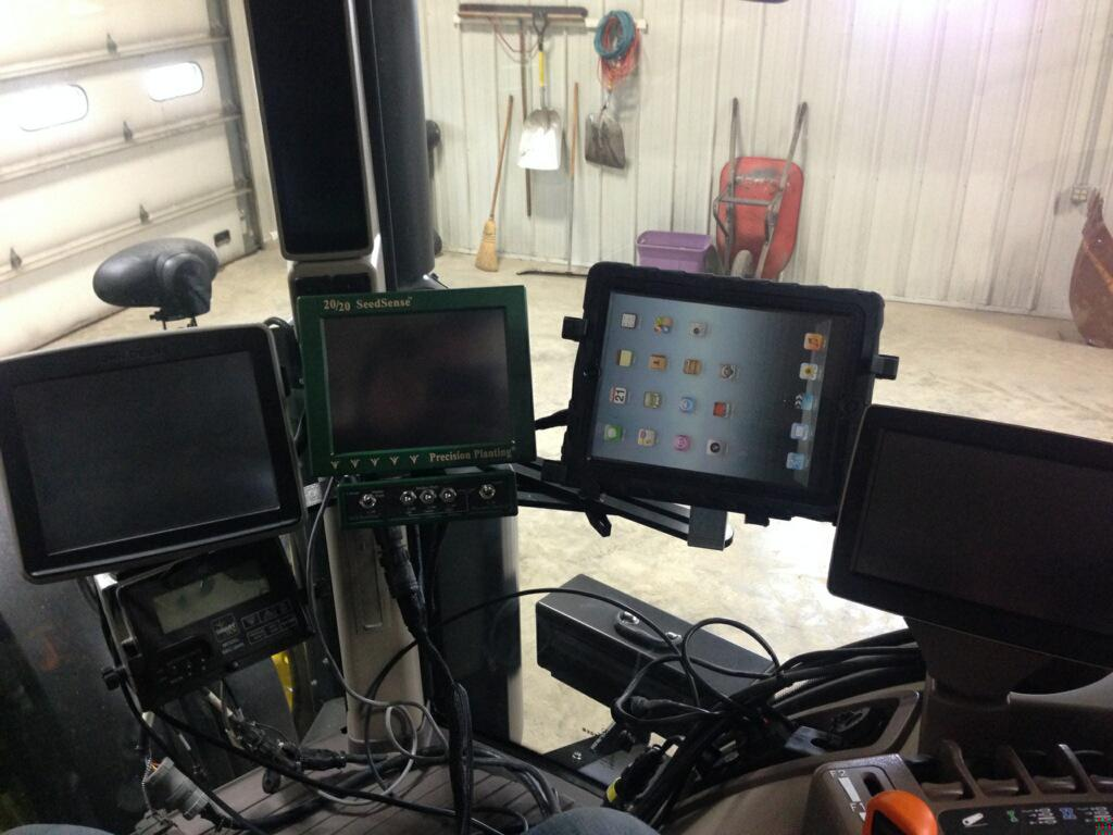 Three electronic screens, a dashboard for a tractor, inside a metal-sided barn.