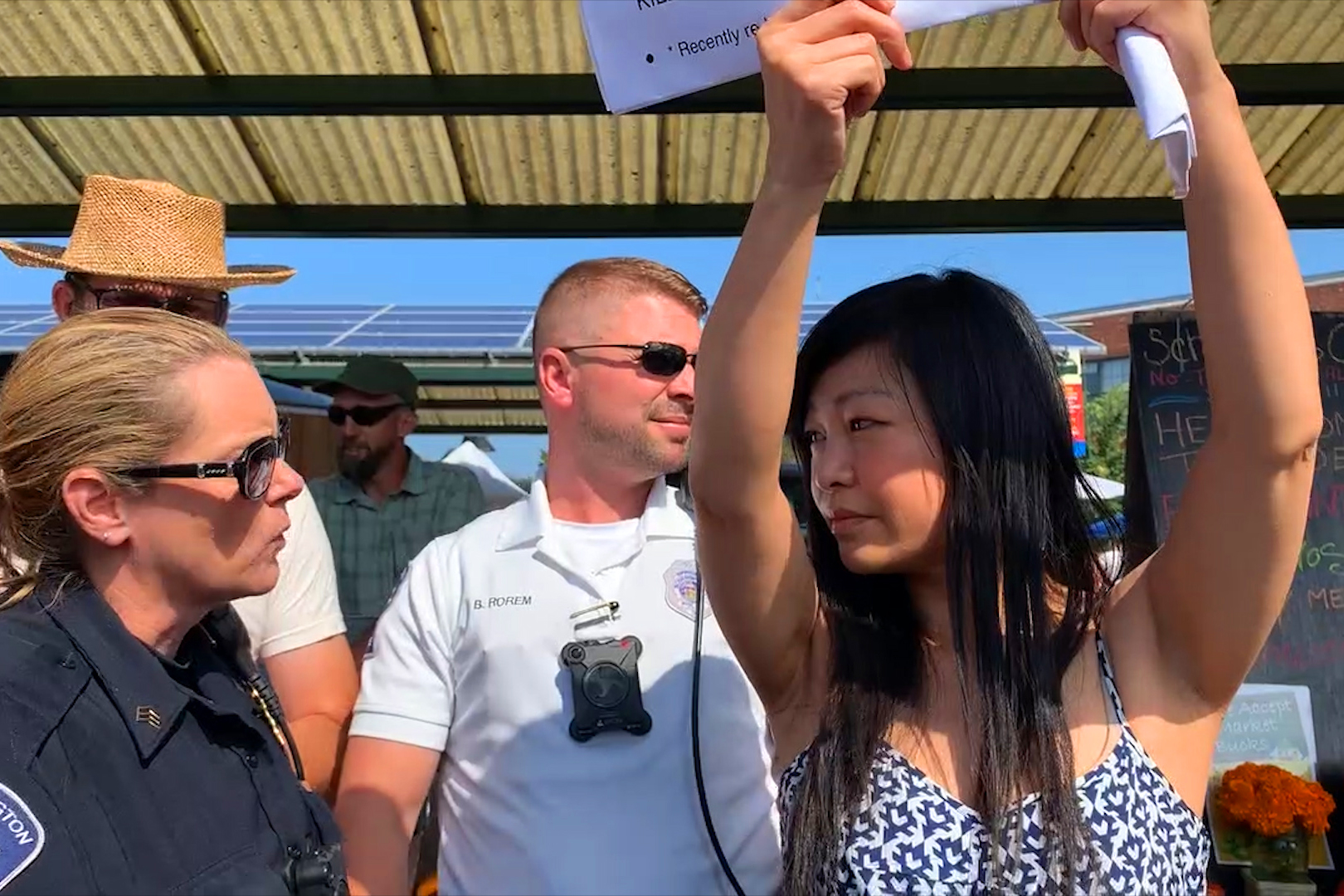 A woman in a sundress, arms holding up a sign, speaking to a female police  officer, with a male cop and a male market vendor visible behind her.