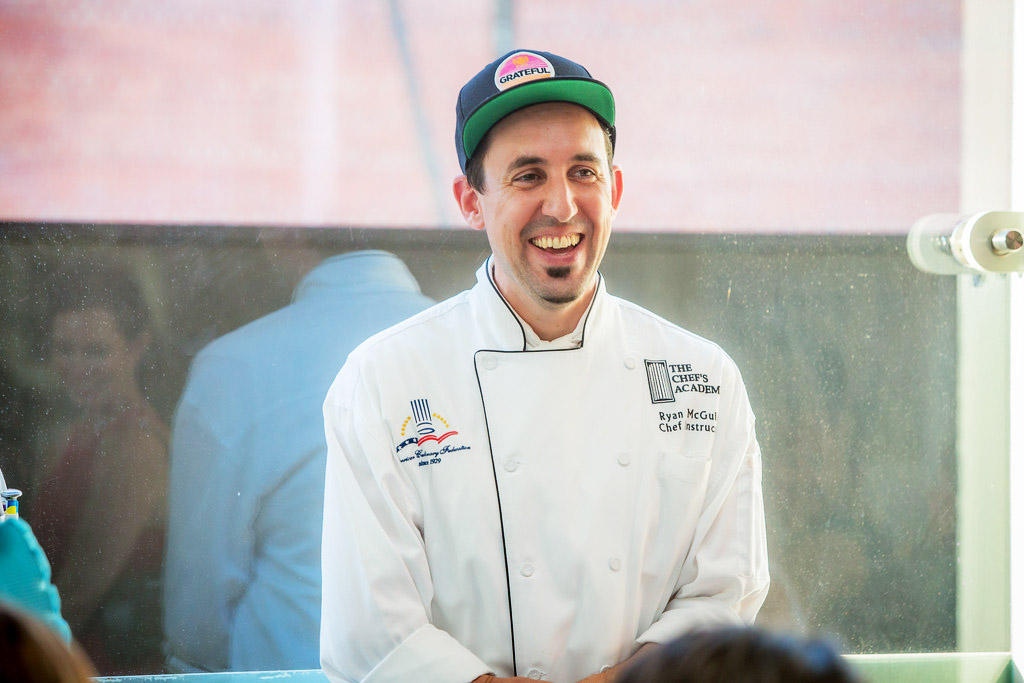 Ryan McGuire, a young white man in a chef's jacket and ballcap, smiling