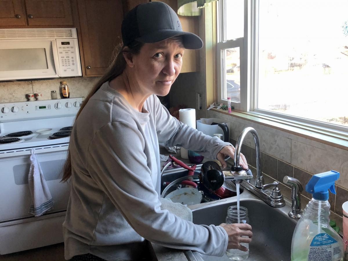 Cheryl LeFevre standing at a kitchen sink filling a mason jar with tap water, and looking at the camera with a worried expression