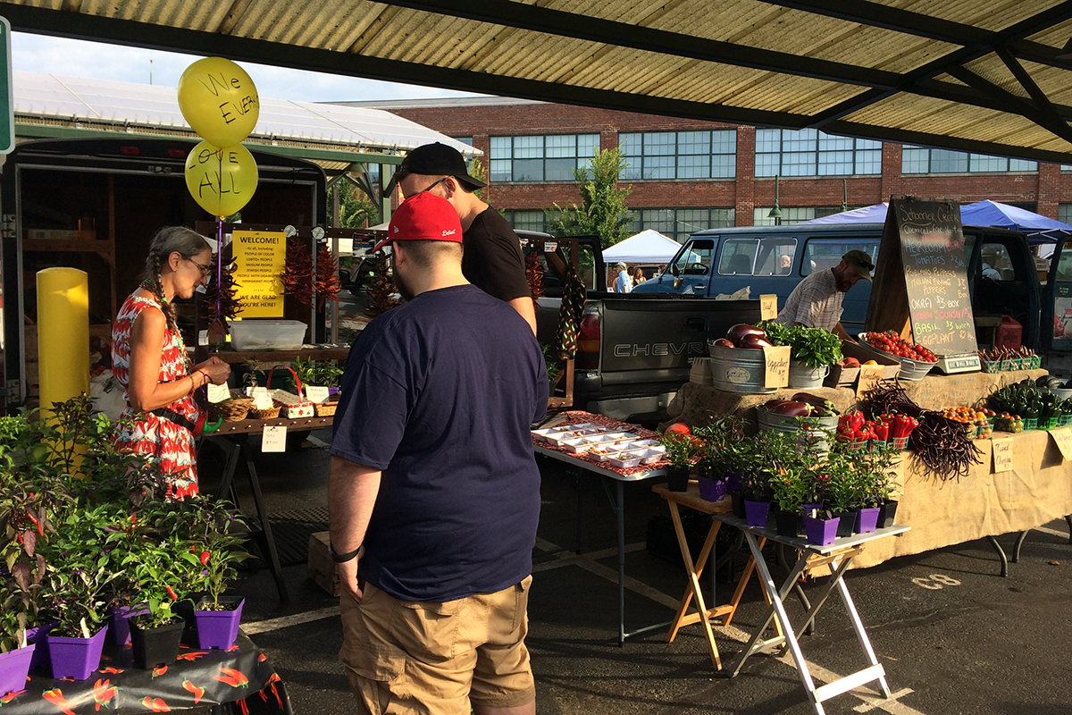 A stand at a farmers market, with chiles, plants and a woman with two yellow balloons, plus two guys with their backs to the camera