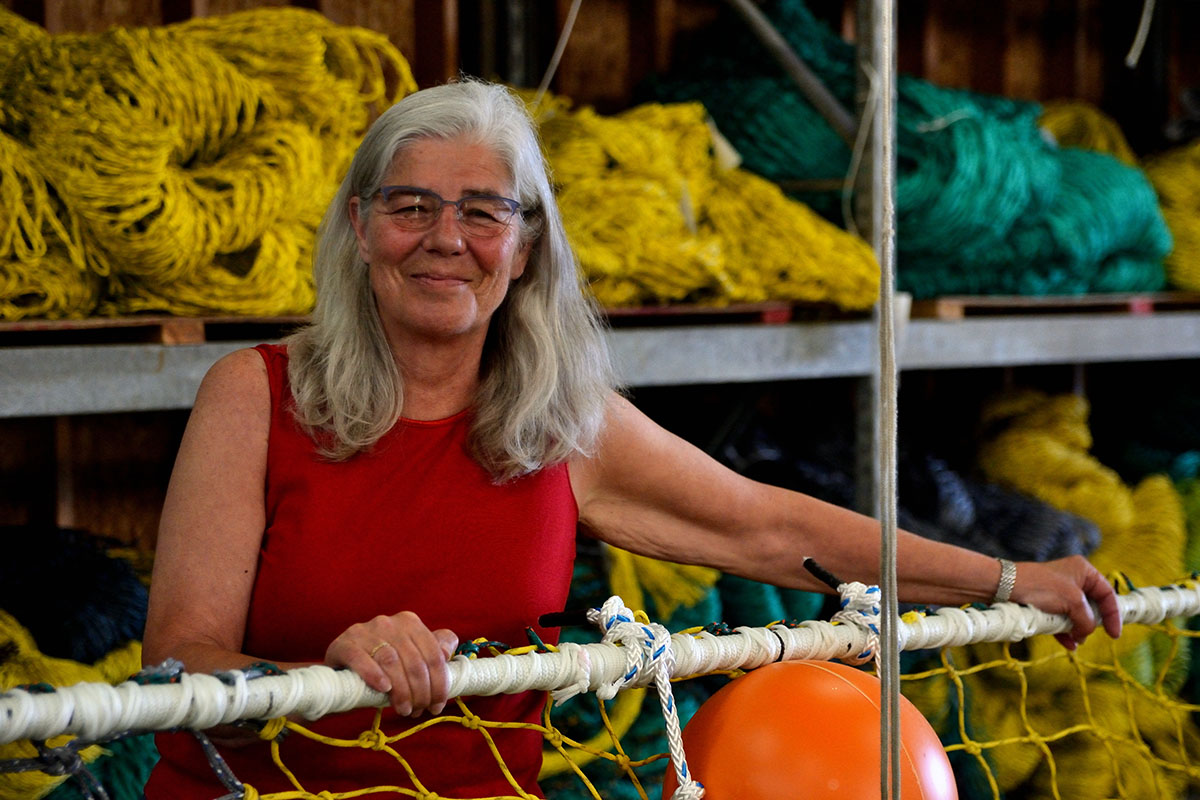Sara Skamser with hands on a commercial fishing net, with net making supplies in the background
