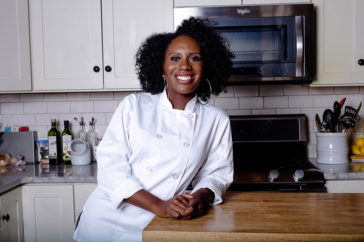 Samantha Kotey in a chef's jacket leaning on a butcher block counter top in a gleaming kitchen.