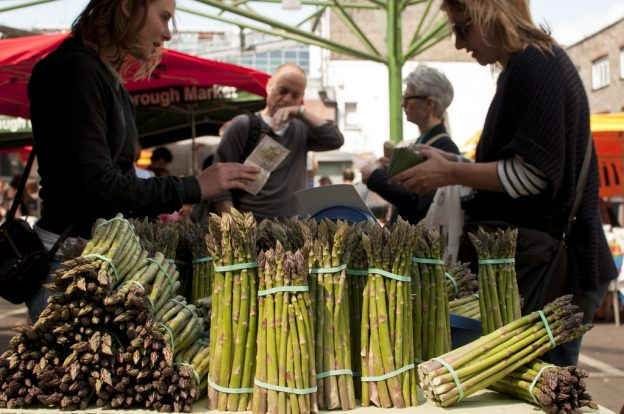 A woman handing money to another woman at a farm stand with asparagus in view