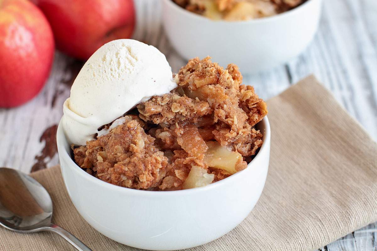 homemade apple crisp or crumble topped with vanilla ice cream in white bowl on linen napkin with apples in background