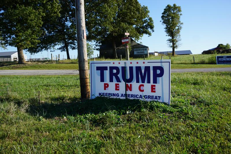 A large Trump/Pence sign on a rural road with barns in the background.