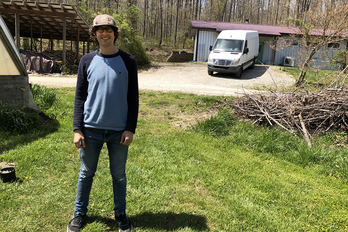 Eric Schedler standing in the grass next to a greenhouse with covered wood pile, white van and metal-sided building and dense woods in the background.