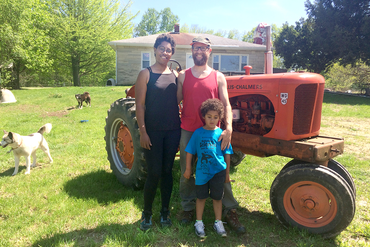 Lauren McAllister, Brett Volpp and young son Jasper in front of old red tractor with house and dogs in the background.