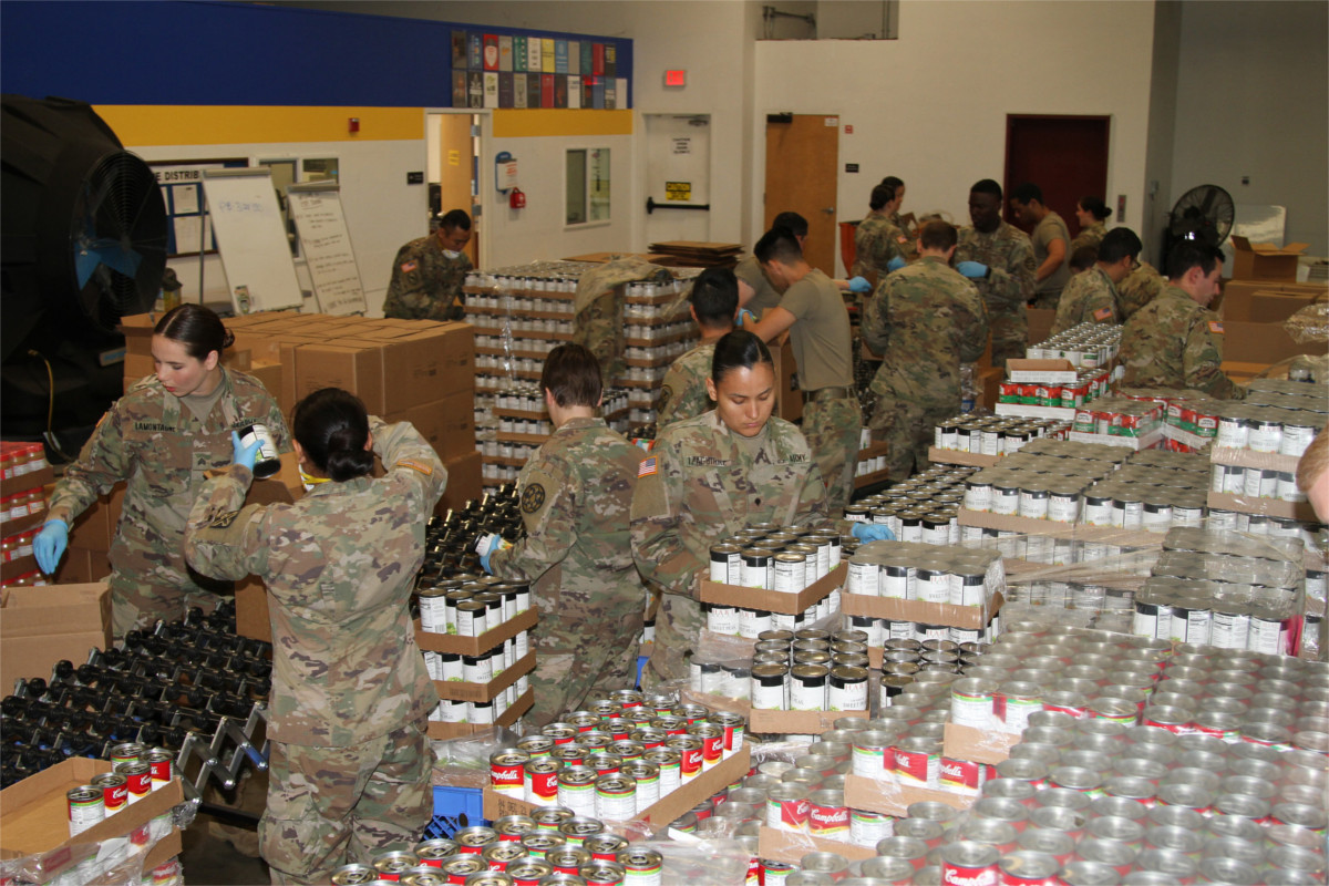 Men and women in military fatigues packing boxes of non-parishable food in a warehouse.