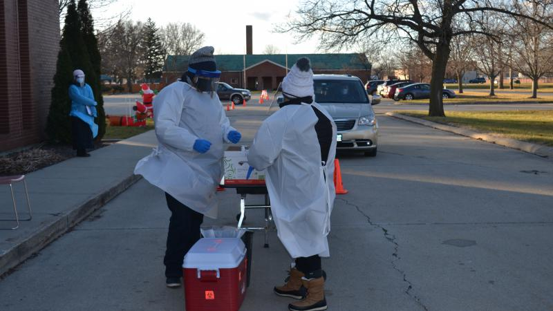 Two people in white medical protective gowns and winter hats stand at a table near a cooler outside in a parking lot as a car drives towards them