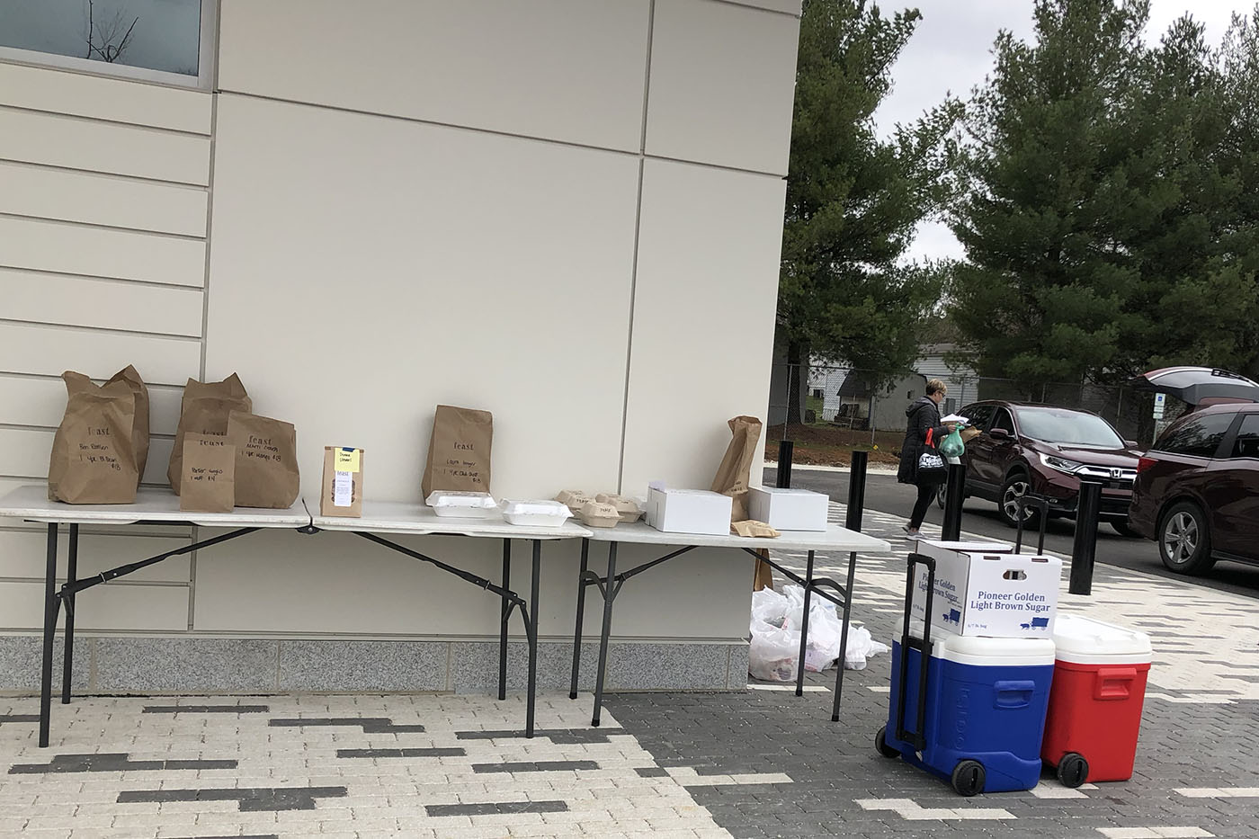 Bags and containers lined up on a table outside of a building, coolers and a person approaching a car with full bags.