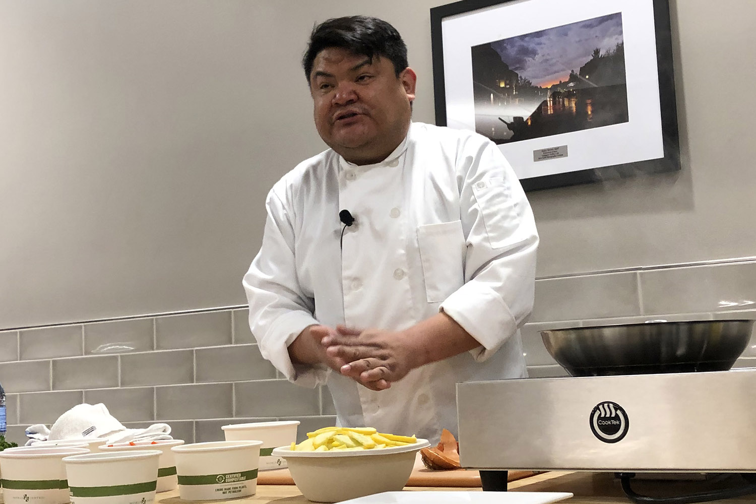 Chef Freddie Bitsoie standing in white chef's jacket at a table with bowls of food and an induction burner.
