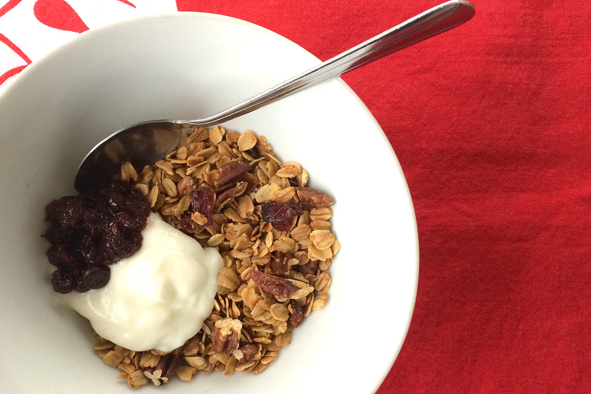 Granola, yogurt and jam in a white bowl on a red background