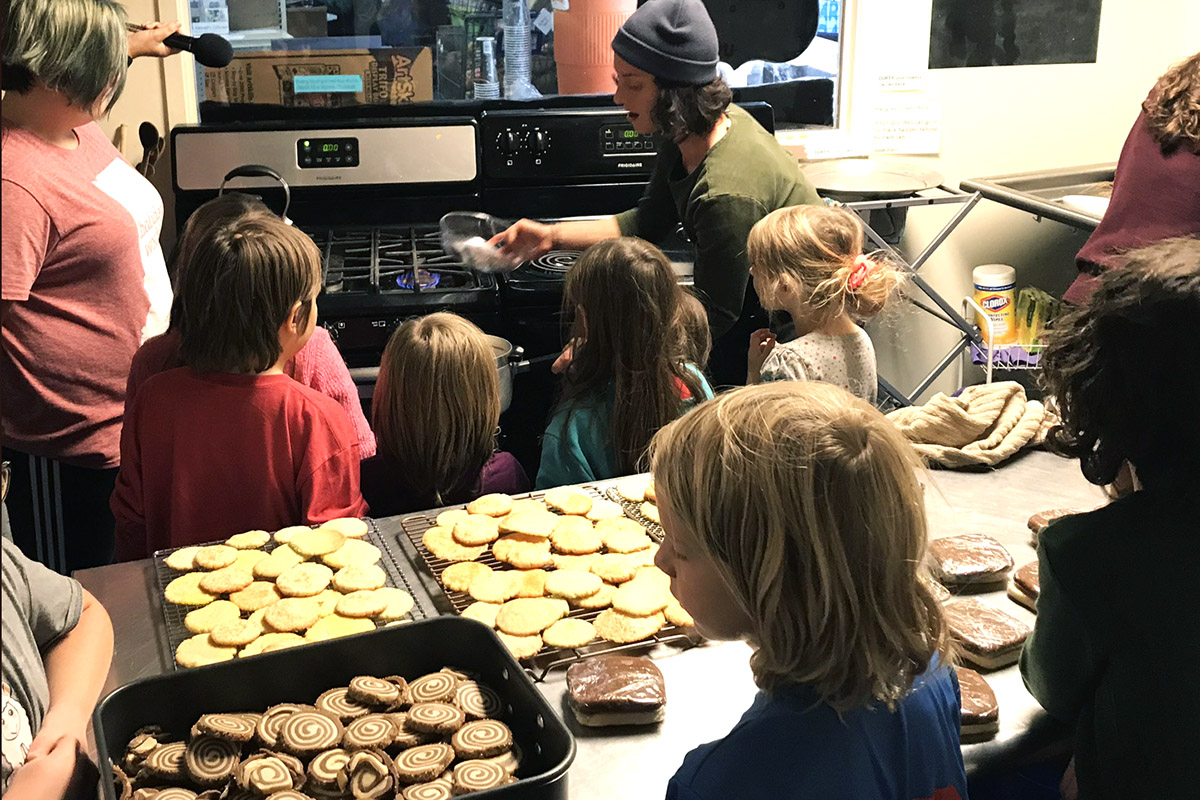 A group of children gathered around a stove with a woman showing them a bowl. Cookies in the foreground