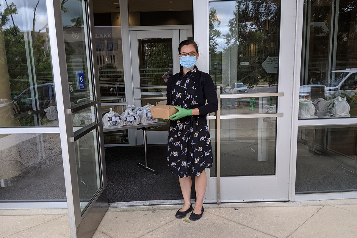 Emmie O'Connor, wearing a face mask and green gloves standing in front of glass doors with a meal box in her hand. Inside the doorway, filled plastic bags line a table.