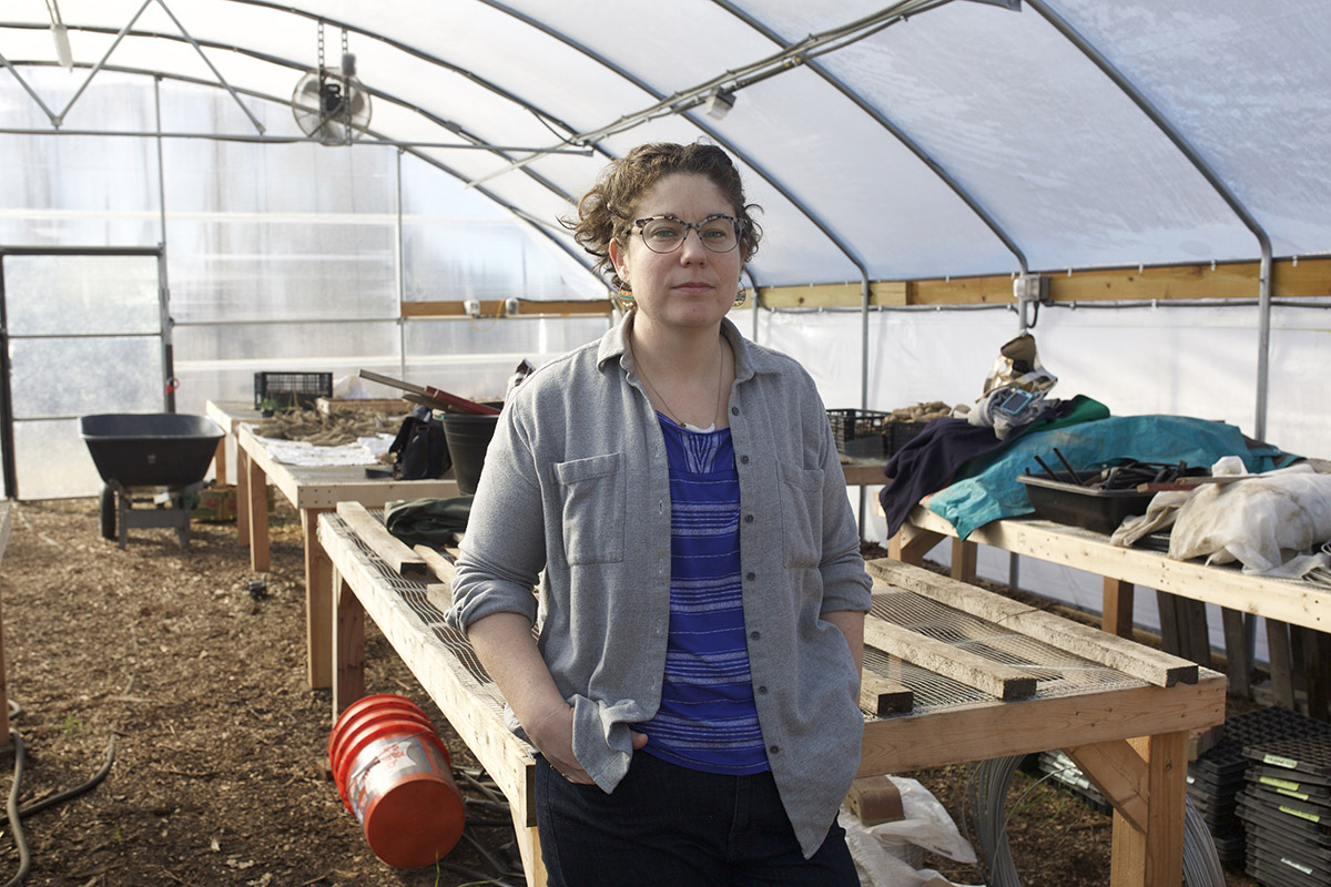 A woman standing in a mostly empty greenhouse, some potatoes and supplies in the background.
