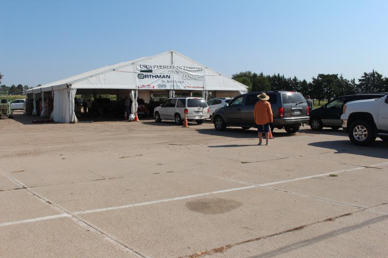 A distanced shot of a large tent with a line of cars heading into the tent and a person standing outside