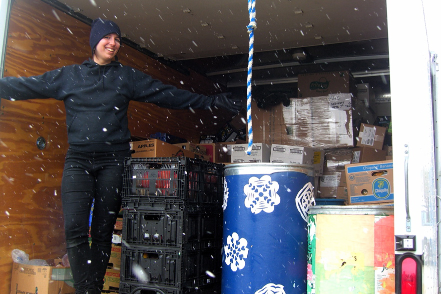 A smiling young woman stands, arms outstretched, in the back of a delivery truck, with snow falling in front of her.