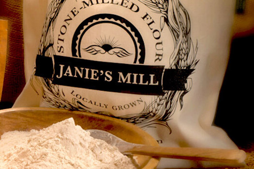 White cloth bag with Janie's Mill printed  in black, behind a bowl of flour